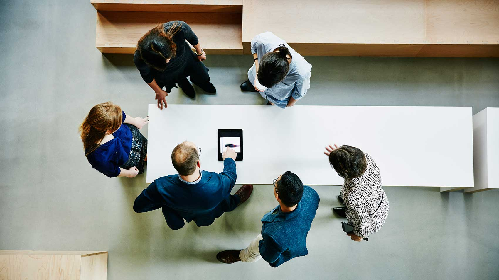 Overhead view of business colleagues discussing project on digital tablet