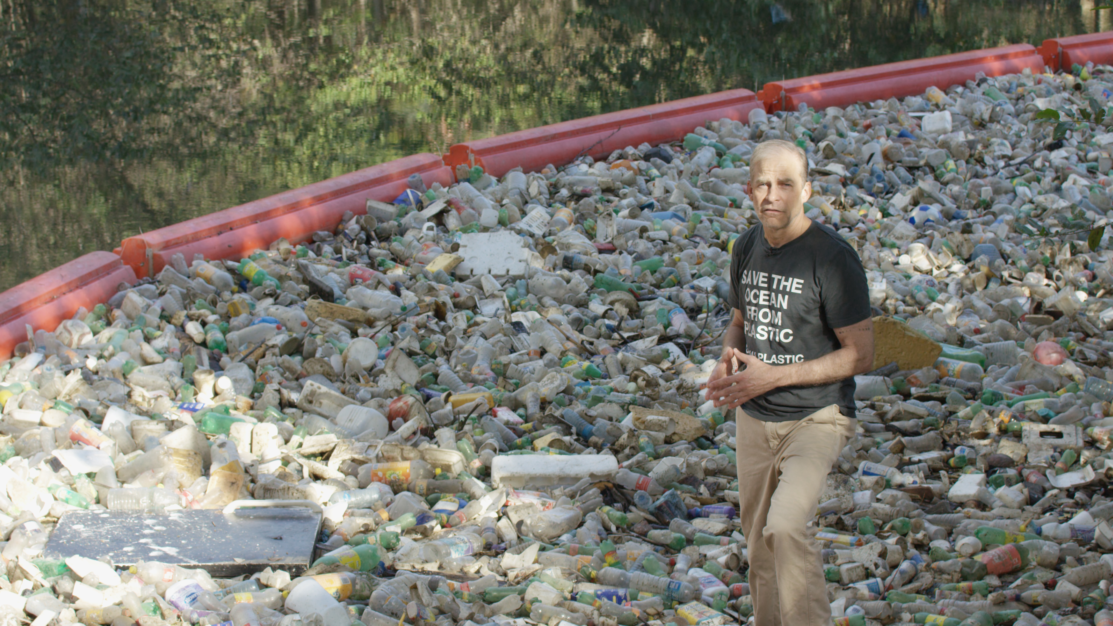 Fisk Johnson at a plastic collection machine in a river