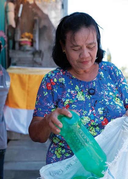 mujer reciclando una botella de plástico