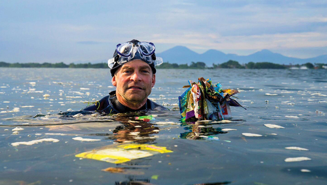Fisk Johnson in the ocean surrounded by ocean plastic