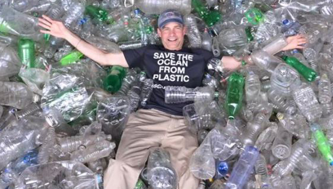 man laying in a bin of recycled plastic bottles.