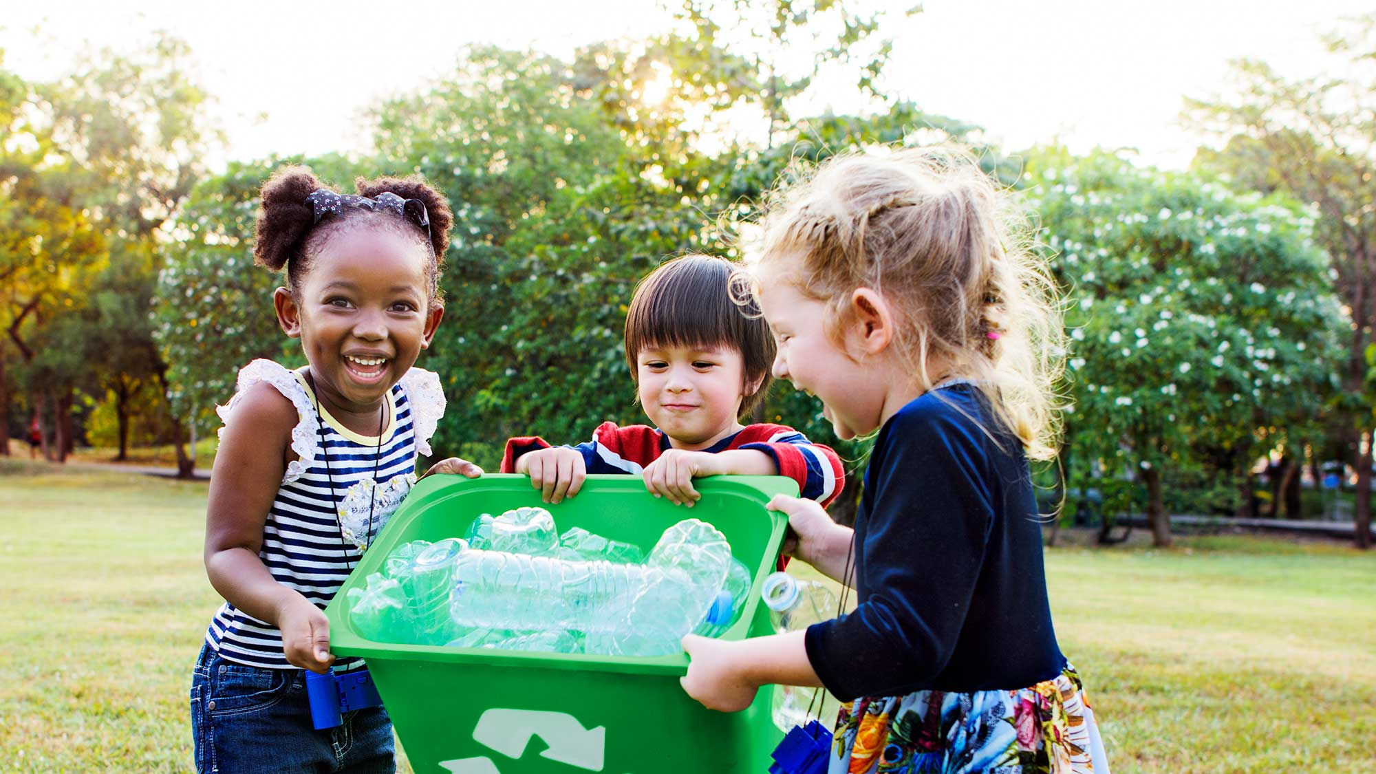 Children gathering recyclables in a green bin.