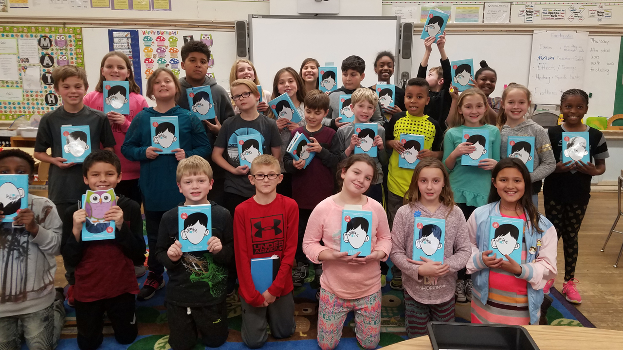 students holding copies of the book Wonder