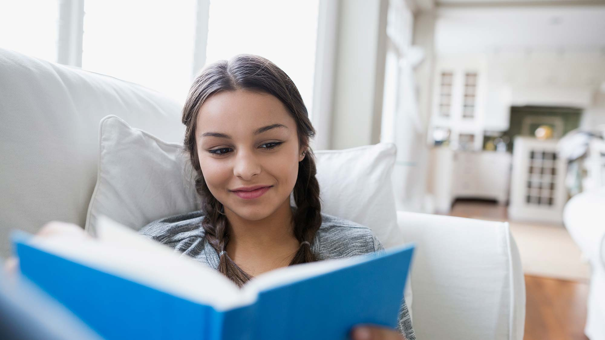 a happy girl reading a book