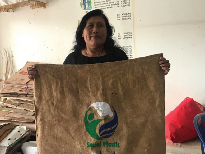 Women holding up Plastic Bank collectors bag.