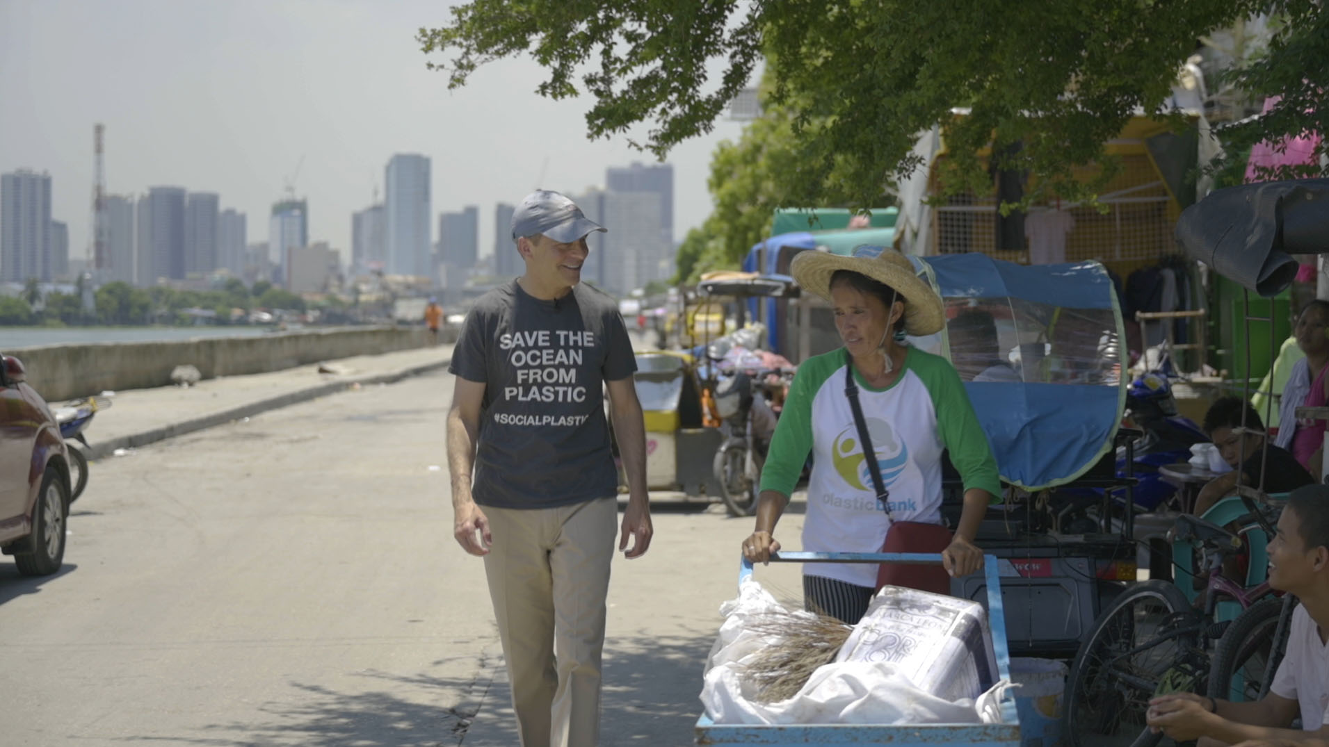 Fisk Johnson walking the street with a plastic collector in Indonesia