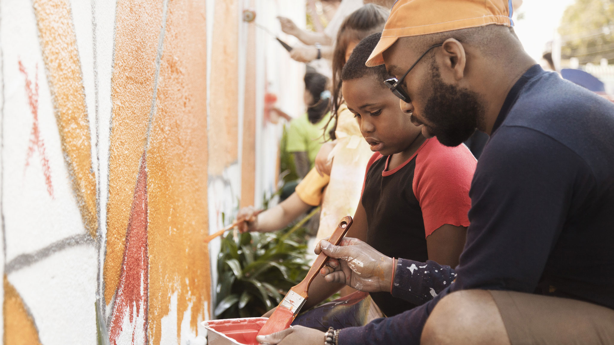 Man helping child paint a wall while volunteering