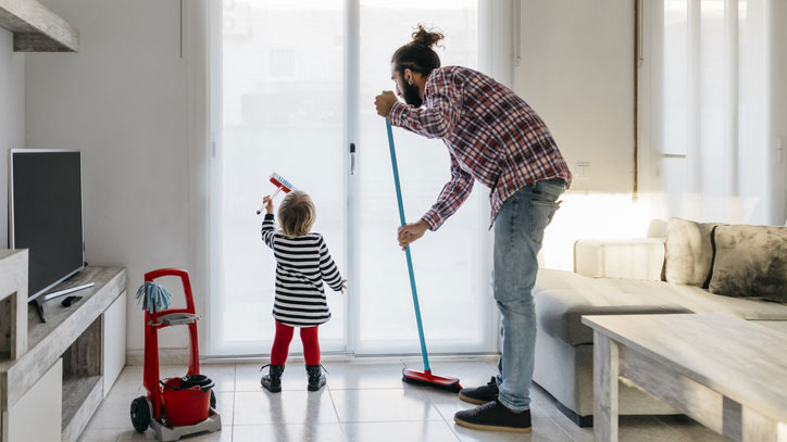Young girl helping her father clean.