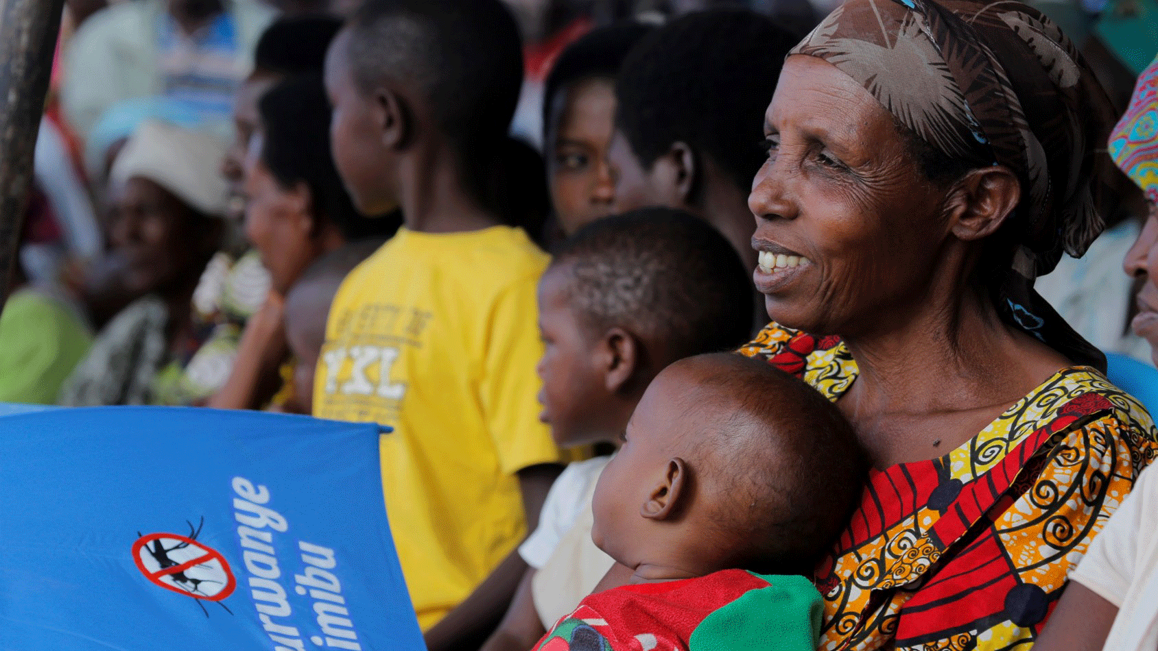 Mother with baby in Rwanda at an educational session on mosquito prevention.