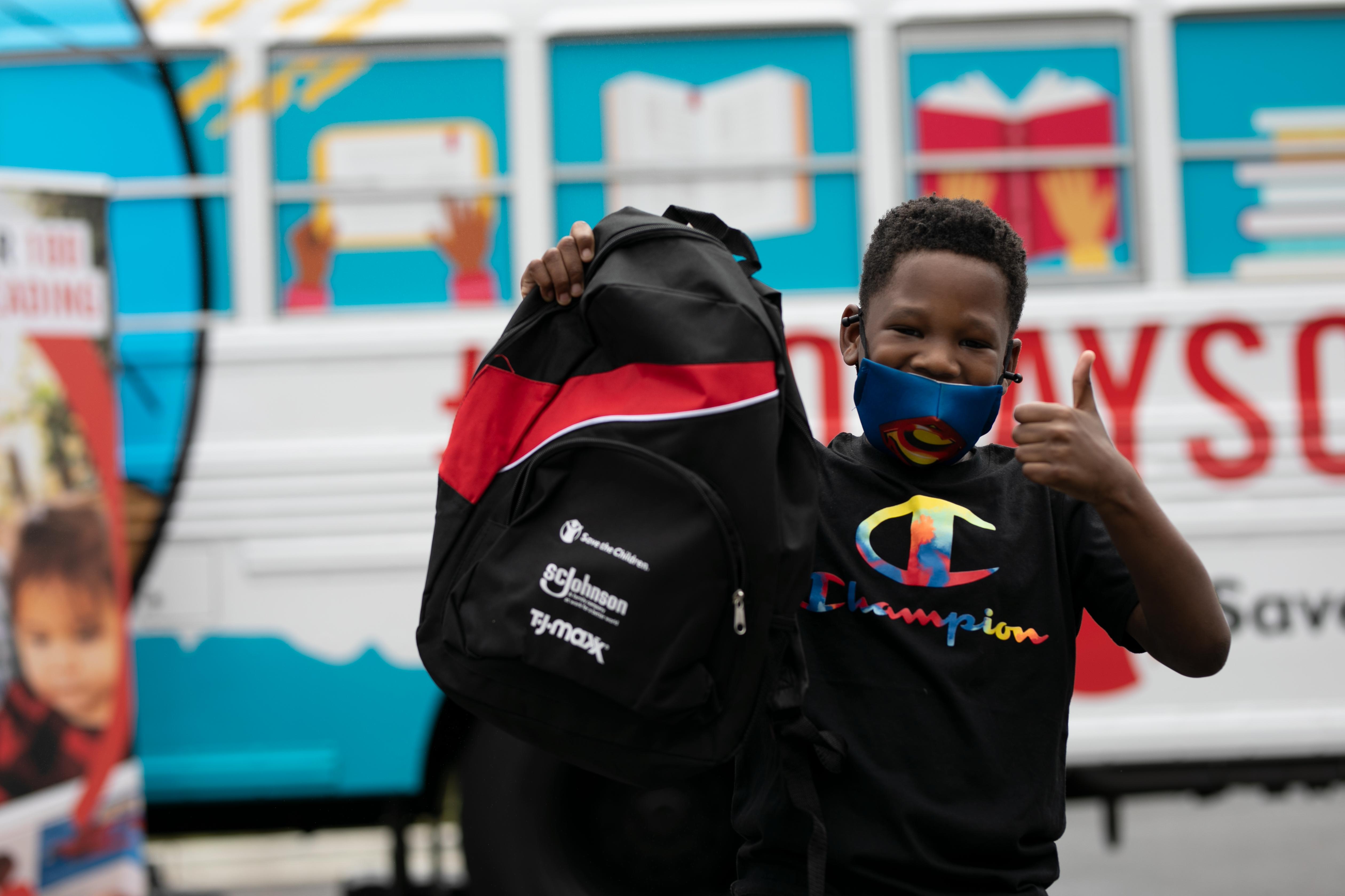 Child Holding Up SC Johnson Sponsored Back pack